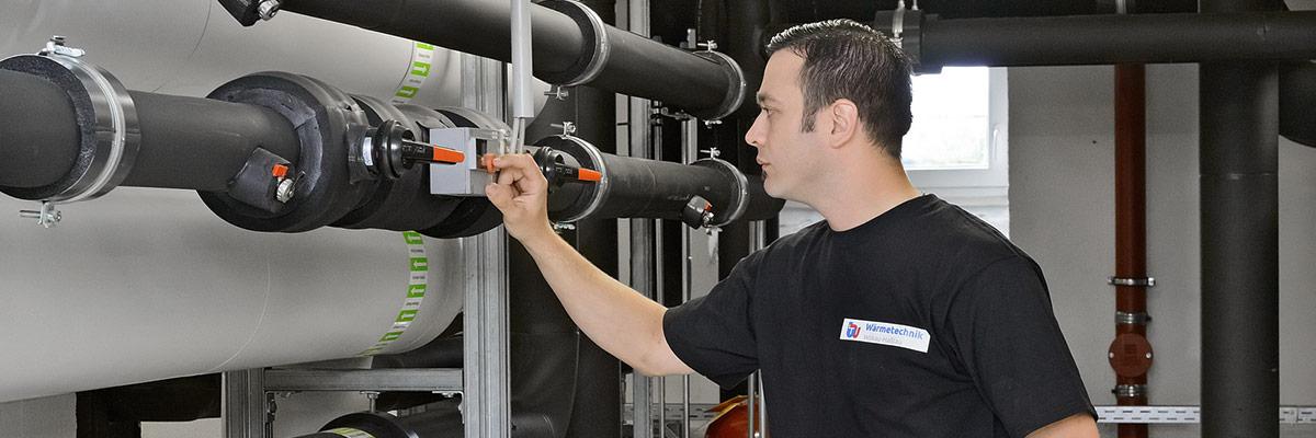 Mitarbeiter von Wärmetechnik kontrolliert Lüftung und Heizung in Zwickau